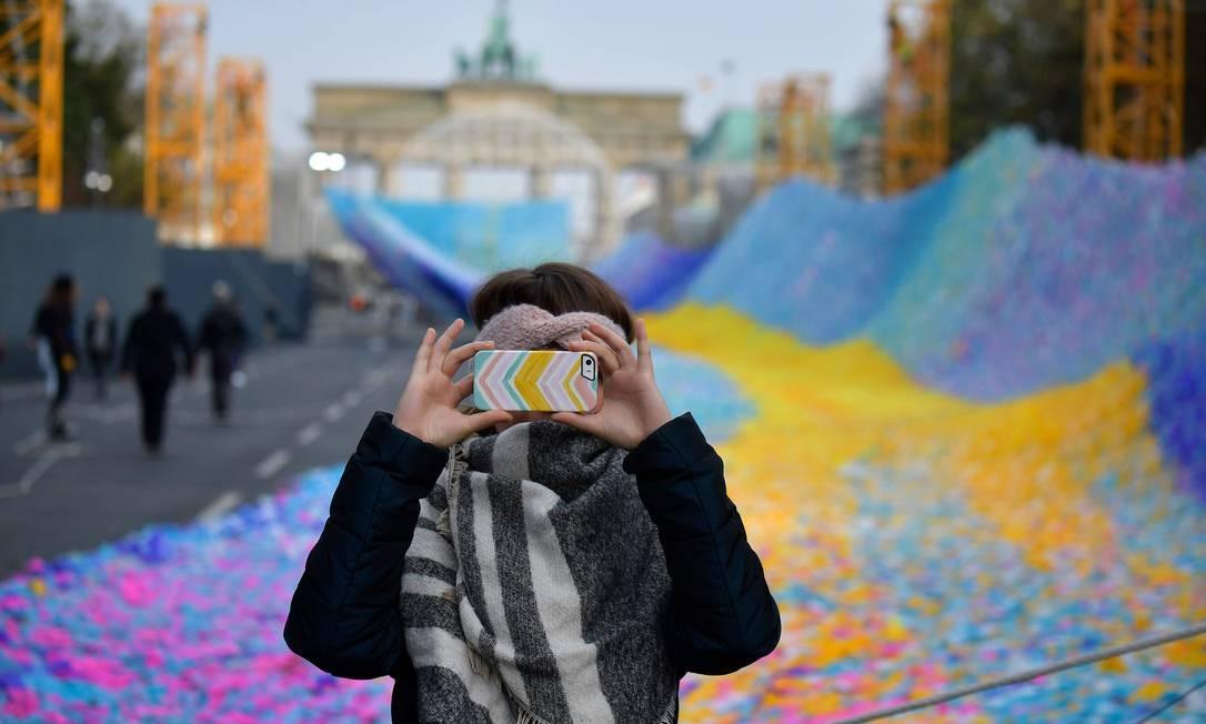 """Uma mulher faz selfies em frente à instalação """"Visões em Movimento"""" do artista Patrick Shearn e seu estúdio Poetic Kinetics durante um teste em frente ao Portão de Brandenburgo, em 1º de novembro de 2019, em Berlim. Enquanto a Alemanha e sua capital, Berlim, comemoram o 30º aniversário da Queda do Muro, a rede feita de 30 mil fitas carrega desejos, esperanças e memórias Foto: TOBIAS SCHWARZ / AFP"""