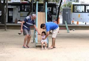 """A passeio no Rio com a família, Públio Batista segura a filha na Praça Julio de Noronha, no Leme: """"Eu nunca tinha pensado sobre a qualidade da areia Foto: Guilherme Pinto / Agência O Globo"""