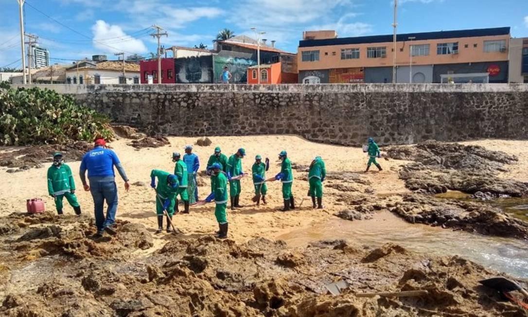 Funcionários trabalham na remoção do óleo na Praia do Rio Vermelho, em Salvador Foto: Luana Assiz/TV Bahia