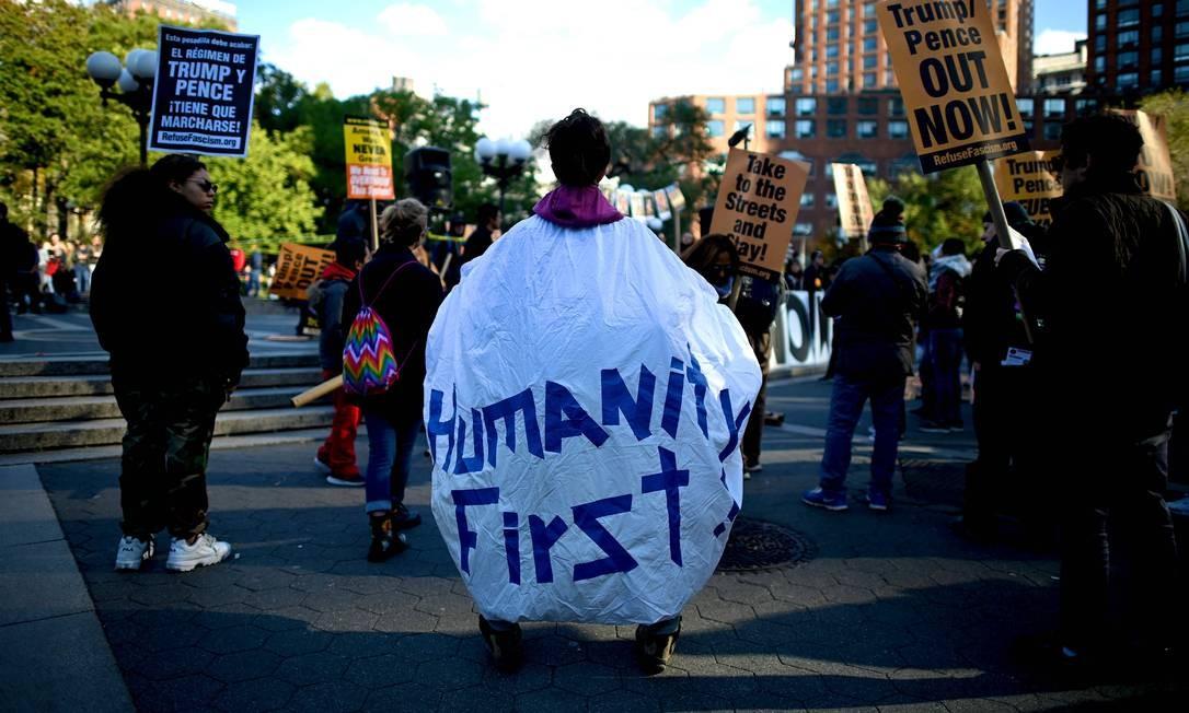 """""""Humanidade primeiro"""" diz cartaz de manifestante. Protesto em Nova Iorque pede a saída de Donald Trump e seu vice Mike Pence Foto: Johannes Eisele / AFP"""