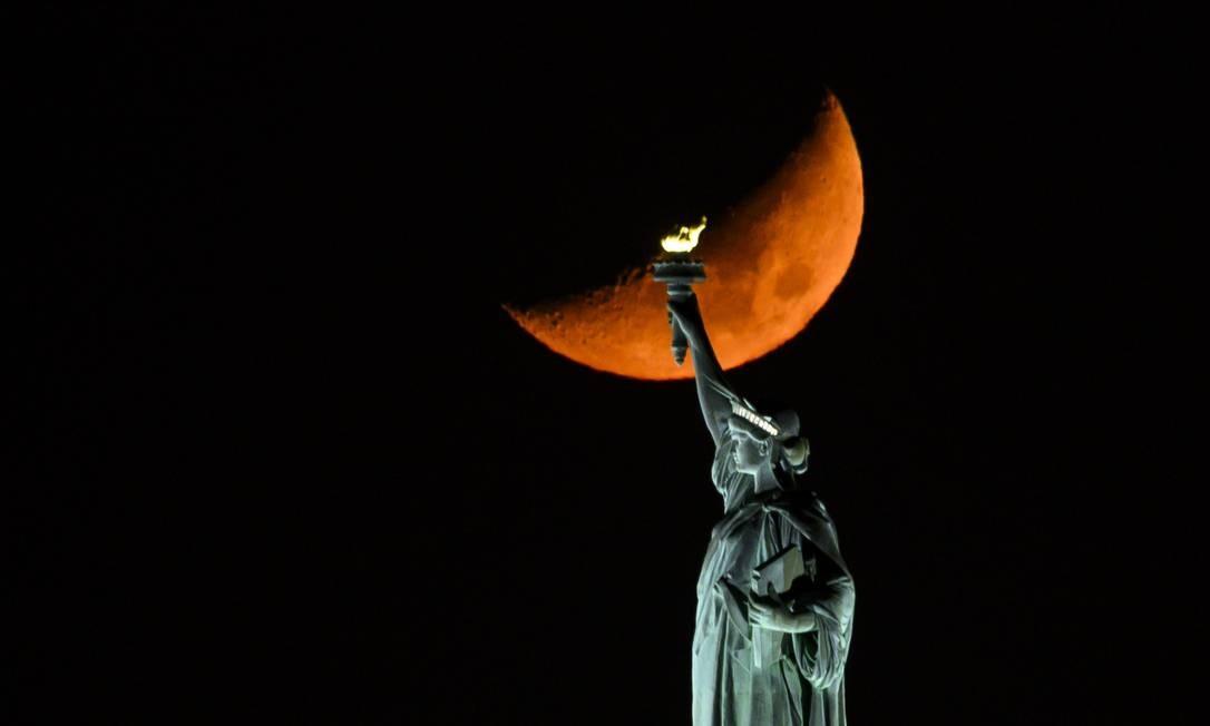 """Fotografia registra lua crescente no momento em que """"toca"""" as chamas da Estátua da Liberdade, nos EUA Foto: Johannes Eisele / AFP"""