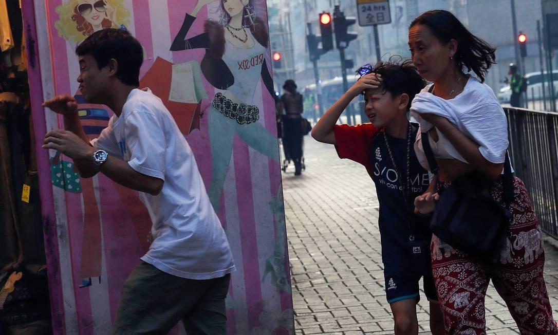 Pessoas correm em Hong Kong de gás lacrimogêneo atirado peloa polícia. Província chinesa enfrenta onda de protestos exigindo a retirada do projeto de lei de extradição, proposto pelo governo Foto: Tyrone Siu / Reuters