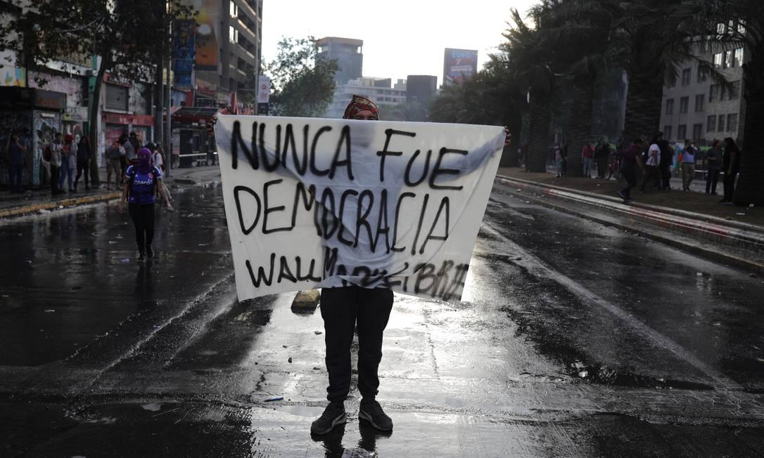 """Manifestante exibe uma placa em que se lê """"Nunca foi uma democracia"""" Foto: PABLO SANHUEZA / REUTERS"""