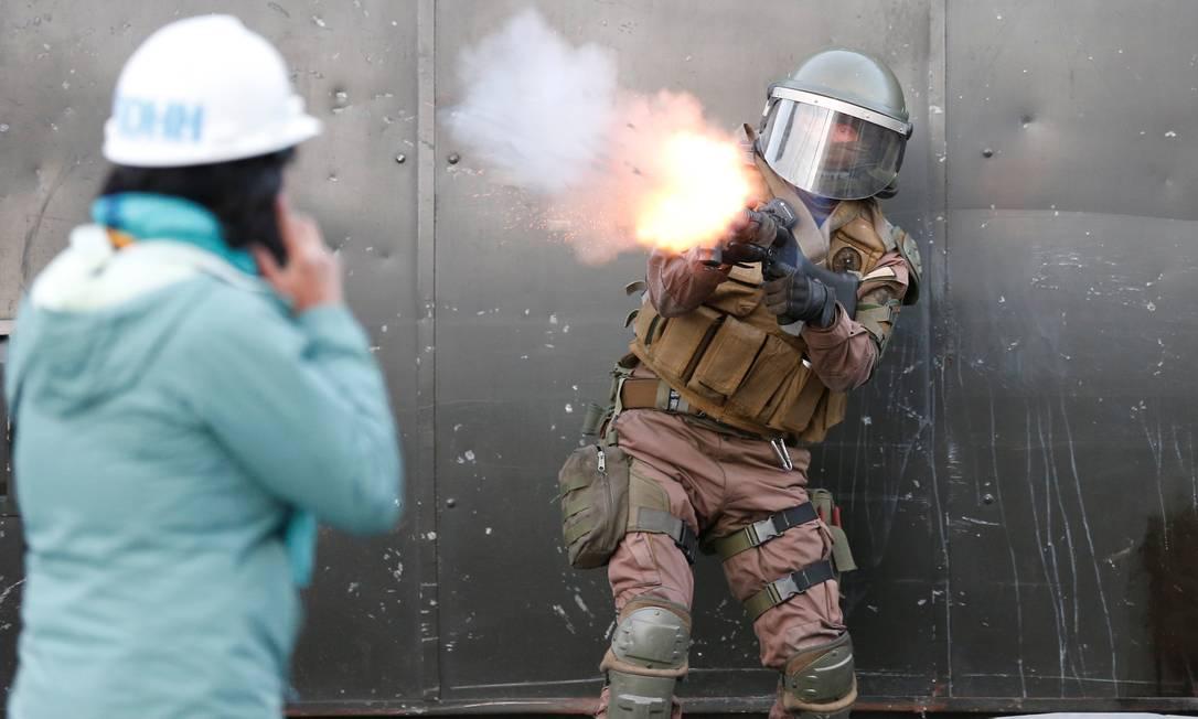 Um policial dispara bomba de gás lacrimogêneo na direção de manifestantes durante um protesto contra o governo do Chile, em Valparaíso Foto: RODRIGO GARRIDO / REUTERS