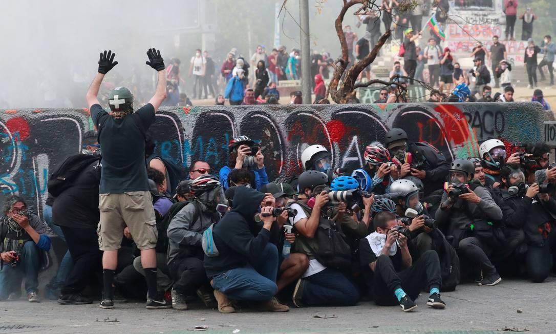 Um homem levanta as mãos perto de um grupo de fotógrafos durante um protesto contra o governo chileno, em Santiago Foto: HENRY ROMERO / REUTERS