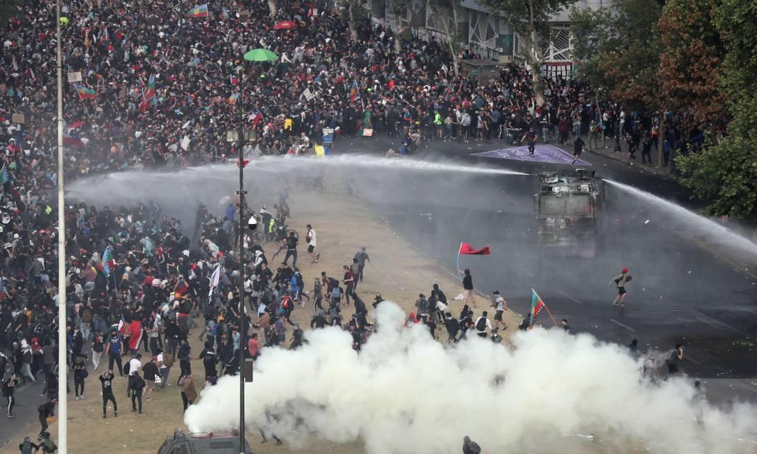 Um veículo da polícia de choque lança um canhão d'água na direção de manifestantes que tomaram as ruas de Santiago nesta segunda-feira (4) Foto: IVAN ALVARADO / REUTERS