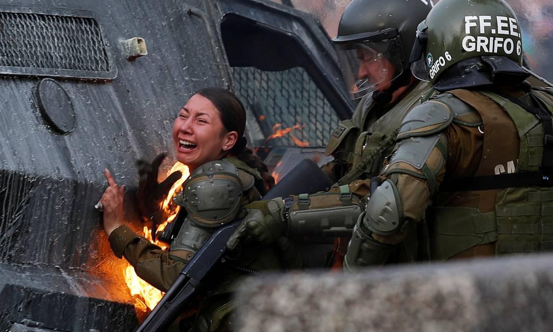 Policiais tentam socorrer colega em chamas durante um protesto em Santiago Foto: JORGE SILVA / REUTERS