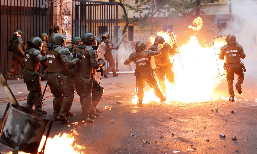 Um policial é atingido por chamas e assistido por seus colegas durante um protesto contra o governo do Chile, em Santiago Foto: JORGE SILVA / REUTERS