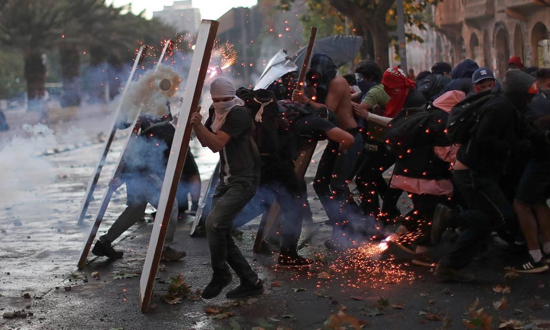 Manifestantes usam escudos improvisados para se proteger de bombas de gás lacrimogêneo lançadas pelas forças de segurança durante protesto em Santiago, Chile. Manifestação reuniu dezenas de milhares de pessoas, a maioria estudantes, para exigir mudanças sociais Foto: JORGE SILVA / REUTERS