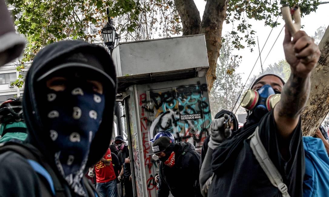 Manifestantes que protestam contra as políticas econômicas do governo do presidente Sebastian Piñera entram em confronto com a polícia em Santiago Foto: MARTIN BERNETTI / AFP