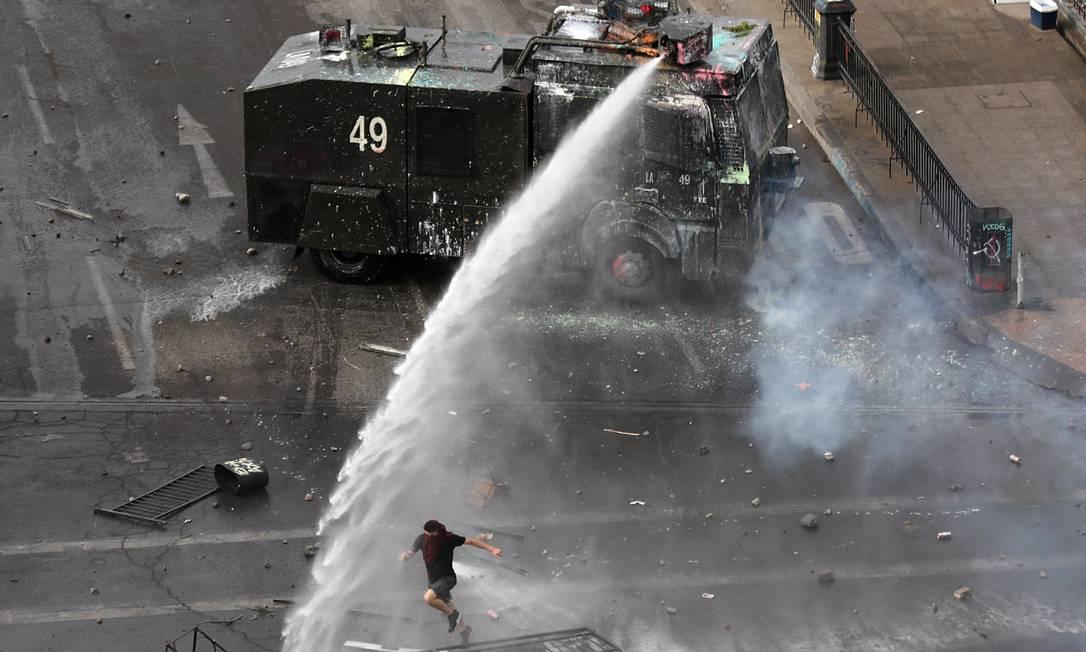 Um veículo da polícia dispara um canhão d'água perto de um manifestante Foto: IVAN ALVARADO / REUTERS