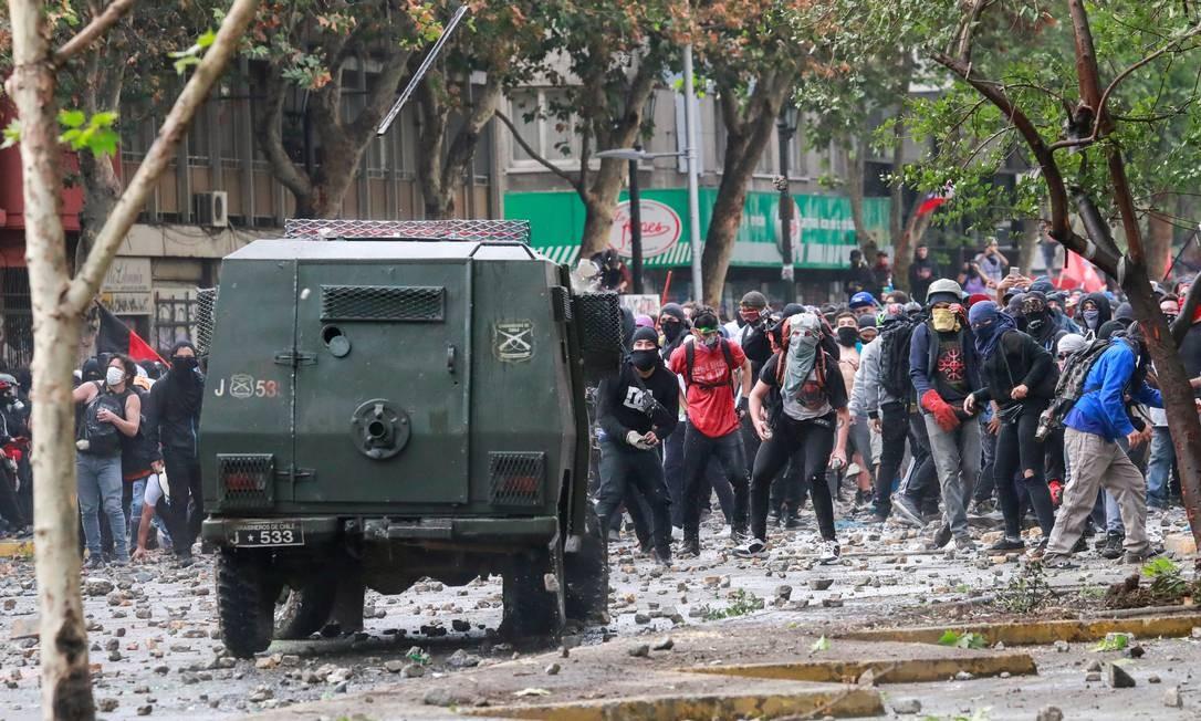 Manifestantes enfrentam um veículo das forças de segurança em rua de Santiago Foto: HENRY ROMERO / REUTERS