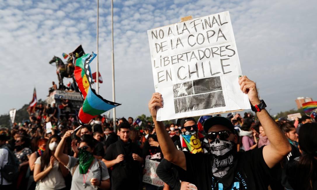 """Um manifestante exibe um cartaz com a inscrição """"Não à final da Copa Libertadores no Chile"""" durante o protesto em Santiago Foto: JORGE SILVA / REUTERS"""