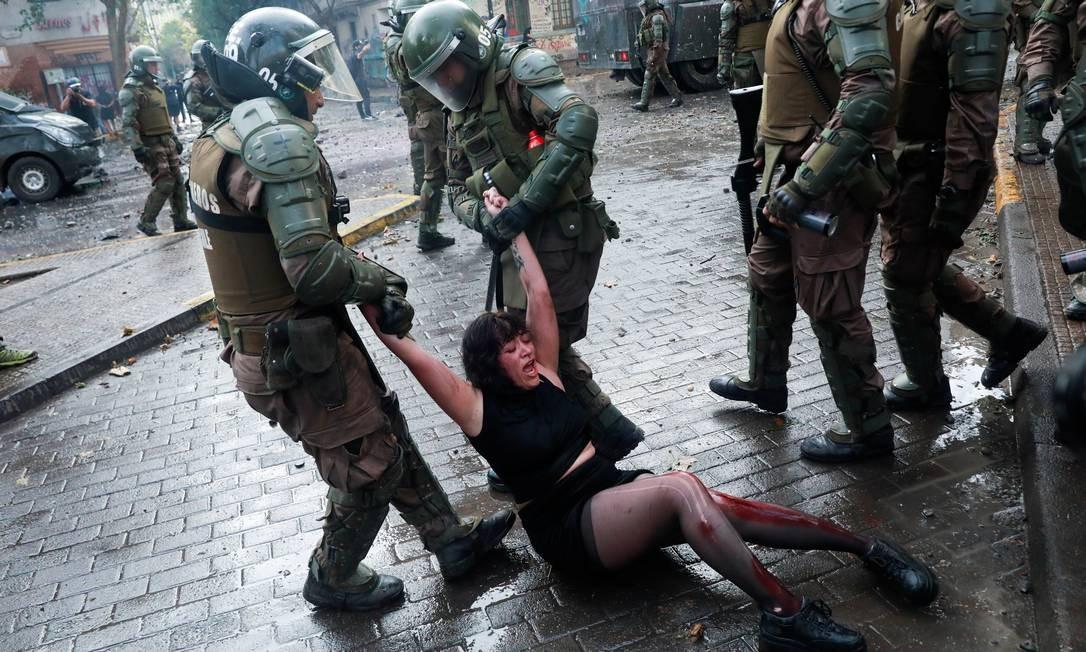 Uma manifestante ferida é detida por membros das forças de segurança Foto: HENRY ROMERO / REUTERS