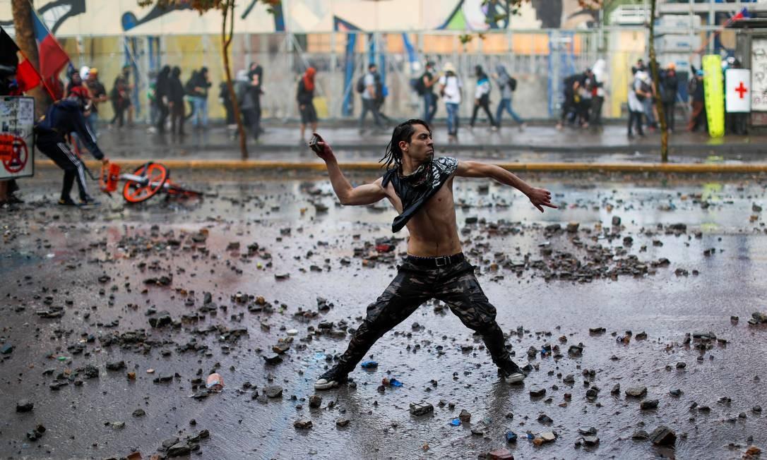 Manifestante joga uma pedra contra policiais durante um protesto contra o governo do Chile, em Santiago Foto: JORGE SILVA / REUTERS