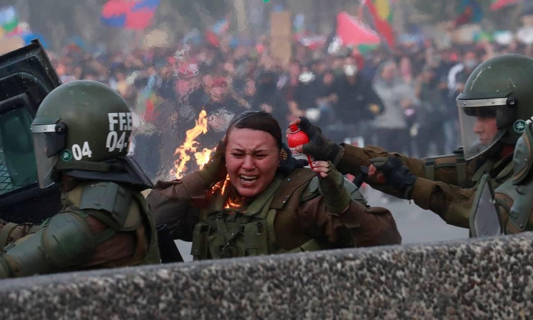 Uma policial pega fogo durante um protesto contra o governo do Chile, em Santiago. Protestos no país entraram na terceira semana nesta segunda-feira (4) Foto: HENRY ROMERO / REUTERS