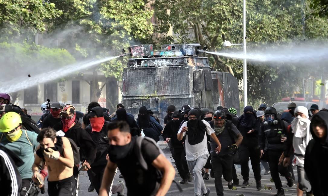 Manifestantes correm enquanto carro da polícia de choque dispara canhões d'ãgua durante confrontos nas ruas da capital chilena Foto: MARTIN BERNETTI / AFP