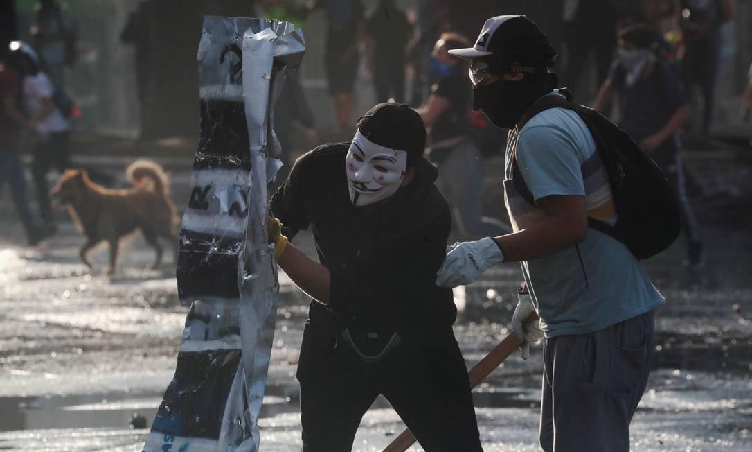 Manifestantes se protegem com escudo improvisado durante protesto em Santiago Foto: HENRY ROMERO / REUTERS