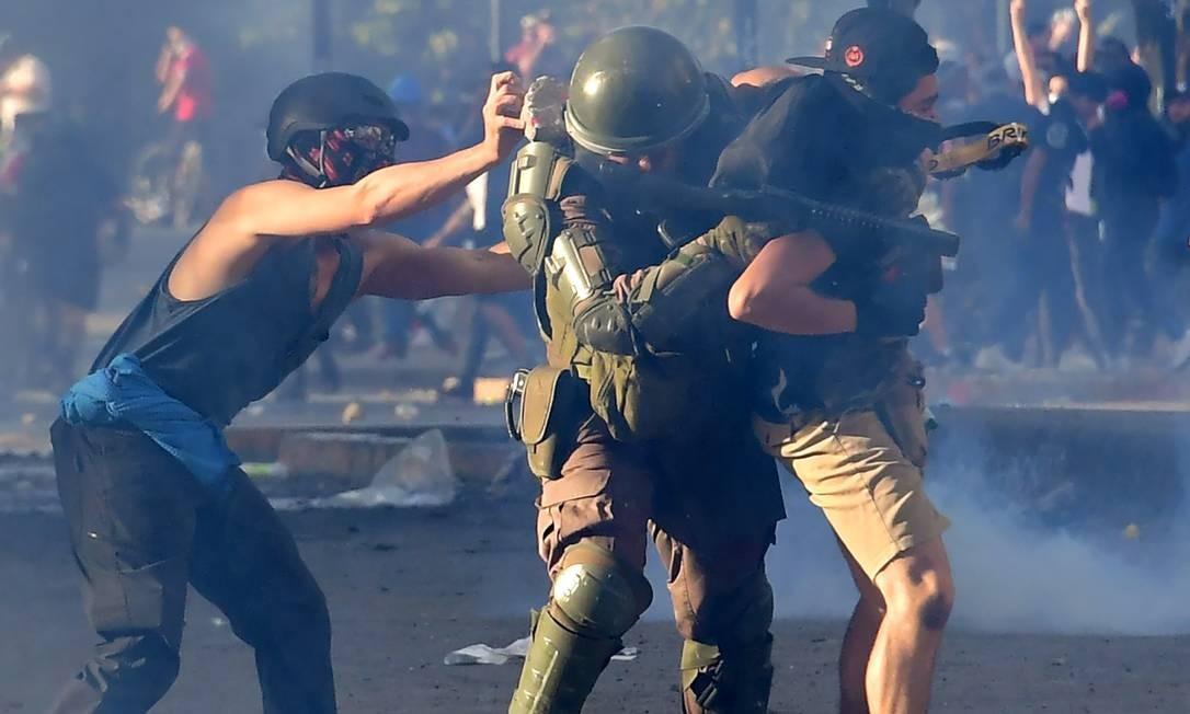 Manifestante ataca com um pedra um policial enquanto ele detém outro manifestante durante os confrontos em Santiago Foto: MARTIN BERNETTI / AFP