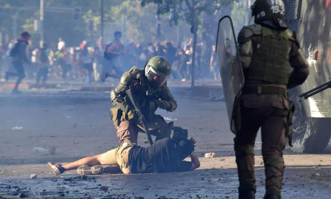 Manifestante é detido pela polícia de choque durante os confrontos em Santiago Foto: MARTIN BERNETTI / AFP