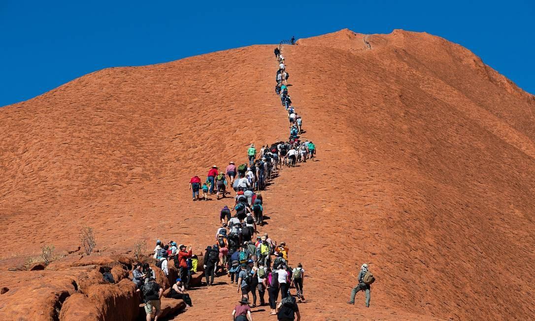 Escaladores em Uluru Foto: MATTHEW ABBOTT / NYT