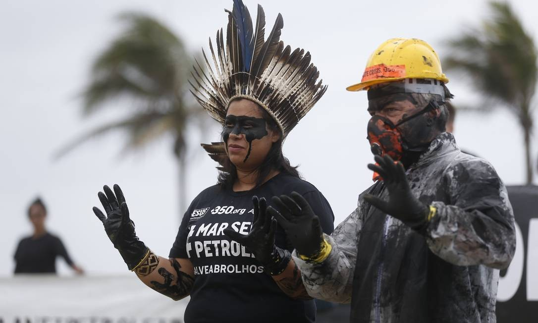 Com as mãos sujas, em alusão ao derramamento de óleo bruto no nordeste, ativistas alertam sobre a chegada de óleo ao arquipélago de Abrolhos, na Bahia Foto: Gabriel de Paiva / Agência O Globo