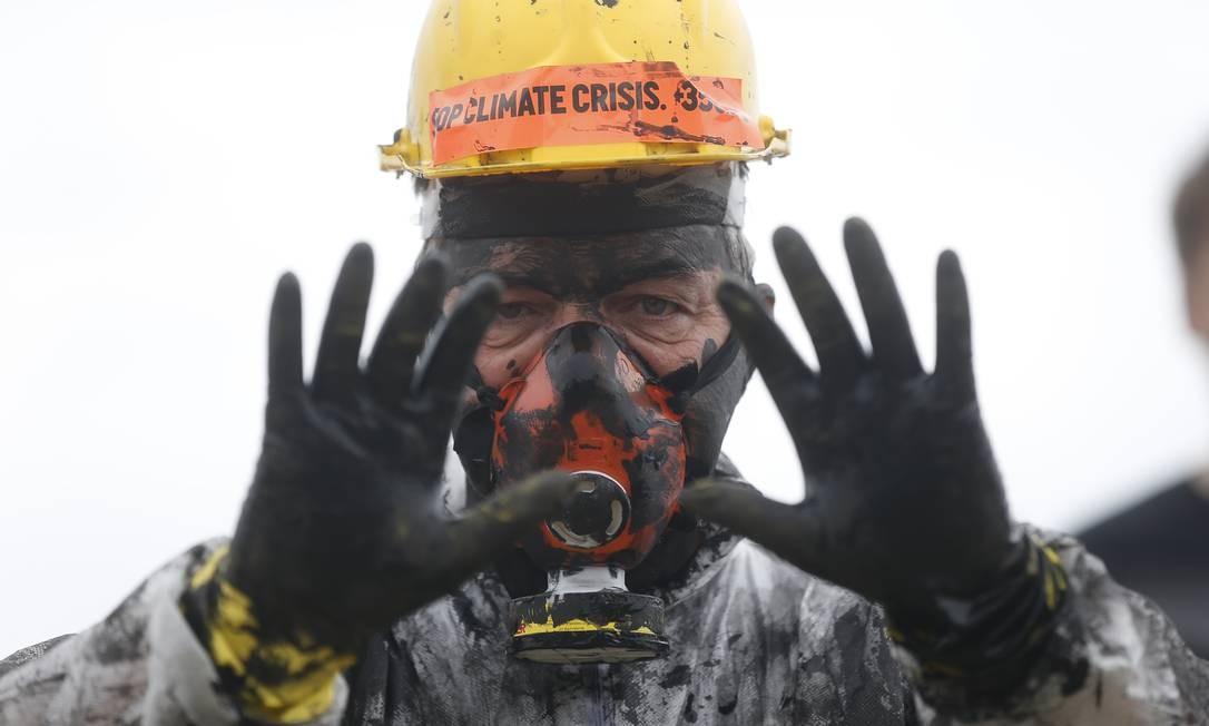 Ativista exibe mãos sujas de óleo, para alertar sobre possíveis desastres ambientais devido à exploração do petróleo Foto: Gabriel de Paiva / Agência O Globo