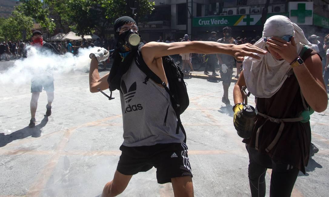 Um manifestante joga de volta um cartucho de gás lacrimogêneo contra policiais Foto: Claudio Reyes / AFP