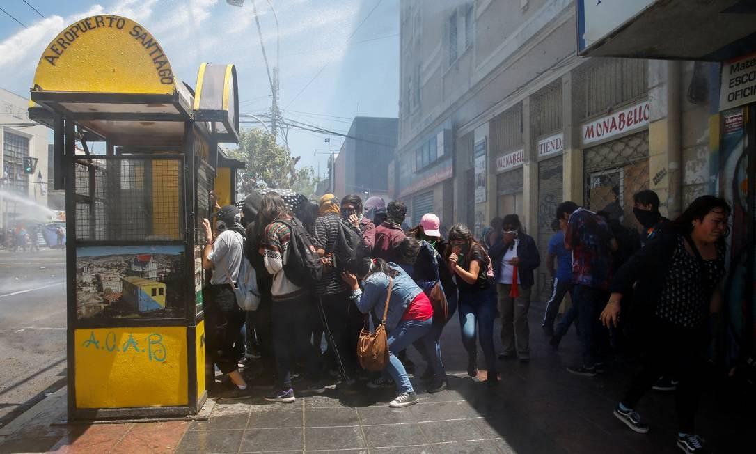 Manifestantes se protegem durante um protesto contra o governo do Chile, em Valparaíso Foto: Rodrigo Garrido / Reuters