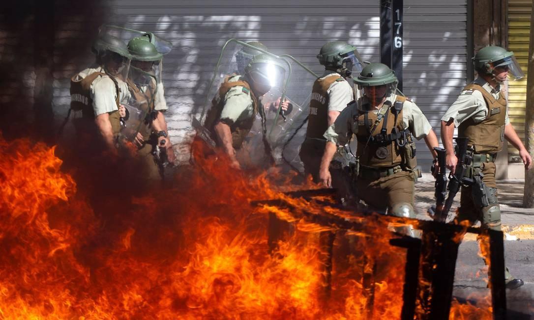 Policiais passam por uma barricada em chamas perto do Centro Costanera Foto: Claudio Reyes / AFP