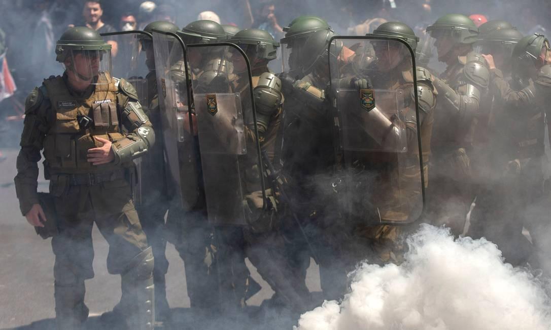 A polícia de choque se posiciona durante um protesto contra as políticas econômicas do governo, perto do Costanera Center Foto: Claudio Reyes / AFP