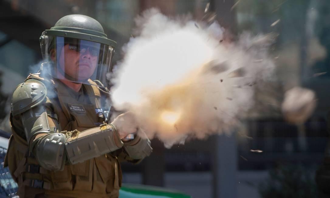Um policial de choque dispara gás lacrimogêneo para dispersar manifestantes durante um protesto próximo ao Centro Costanera Foto: Claudio Reyes / AFP