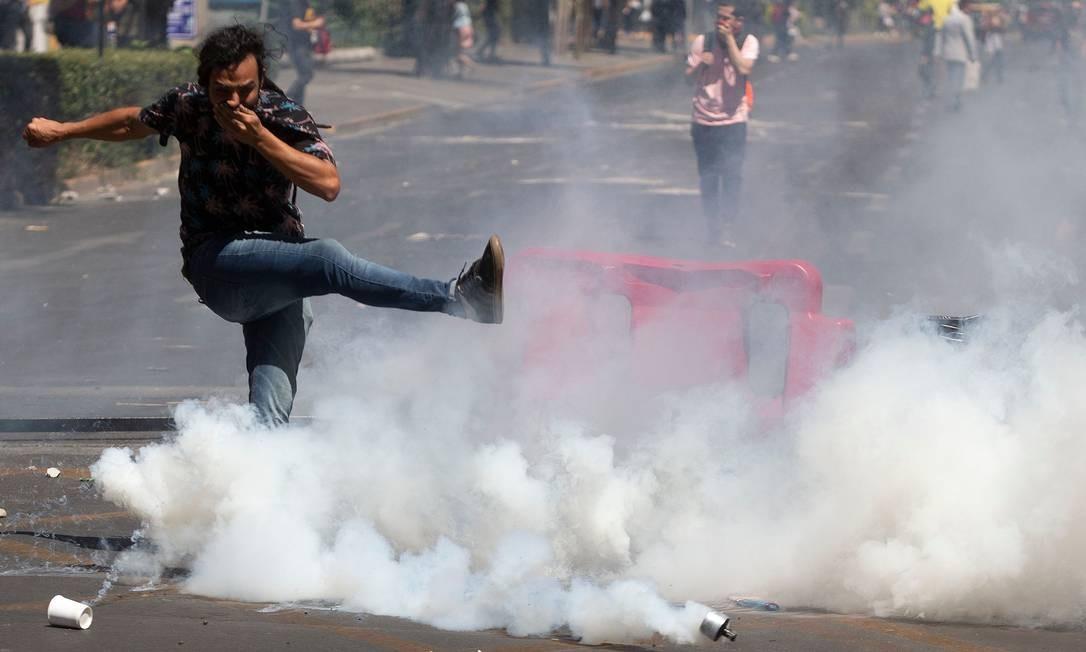 Manifestante chuta uma cápsula de gás lacrimogêneo na direção da polícia durante protesto contra as políticas econômicas do governo, próximo ao Centro Costanera (complexo comercial), em Santiago Foto: Claudio Reyes / AFP