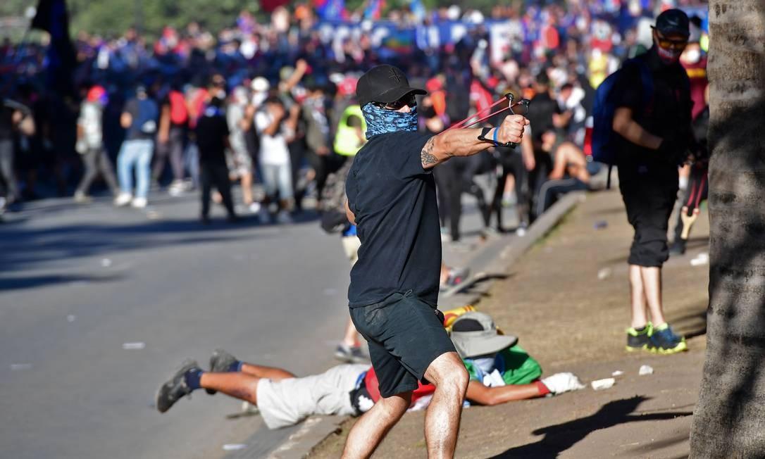 Manifestante usa estilingue para atirar pedras contra policiais durante um protesto em Santiago Foto: Martin Bernetti / AFP