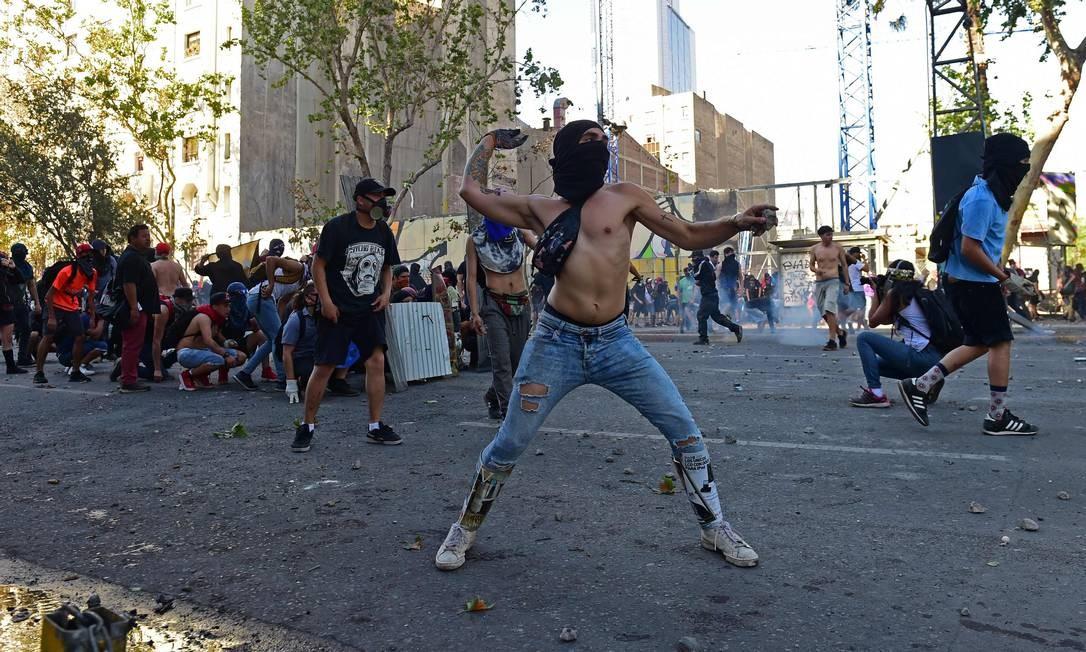 """Manifestantes jogam pedras na polícia durante um protesto antigoverno em Santiago. O presidente do Chile, Sebastián Piñera, disse nesta quarta-feira (6) que não há """"nada a esconder"""" diante das queixas de excessos na repressão policial que se multiplicaram nessas semanas Foto: Martin Bernetti / AFP"""