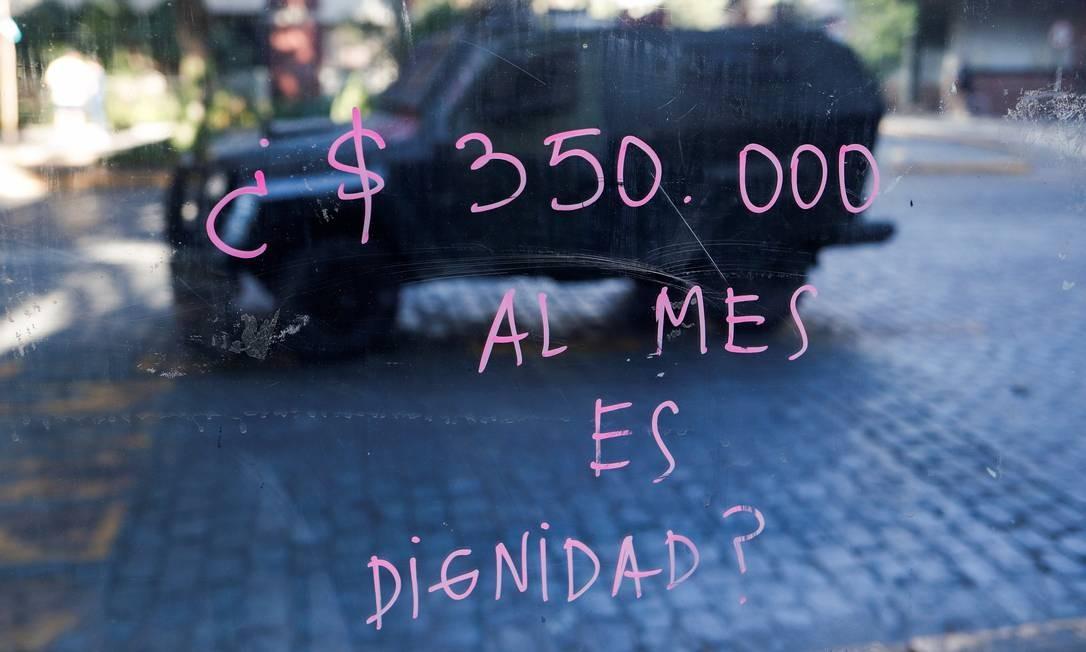 """Um vidro pintado com a inscrição """"US $ 350 por mês é dignidade?"""" reflete um veículo blindado durante um protesto no bairro Providencia Foto: JORGE SILVA / REUTERS"""