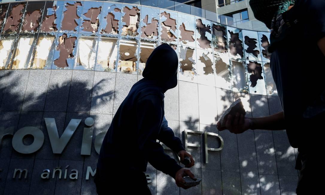 Manifestante atira pedras em vidraças do prédio do Administrador do Fundo de Pensões do Chile (AFP), em Providencia, um bairro rico de Santiago Foto: Jorge Silva / Reuters