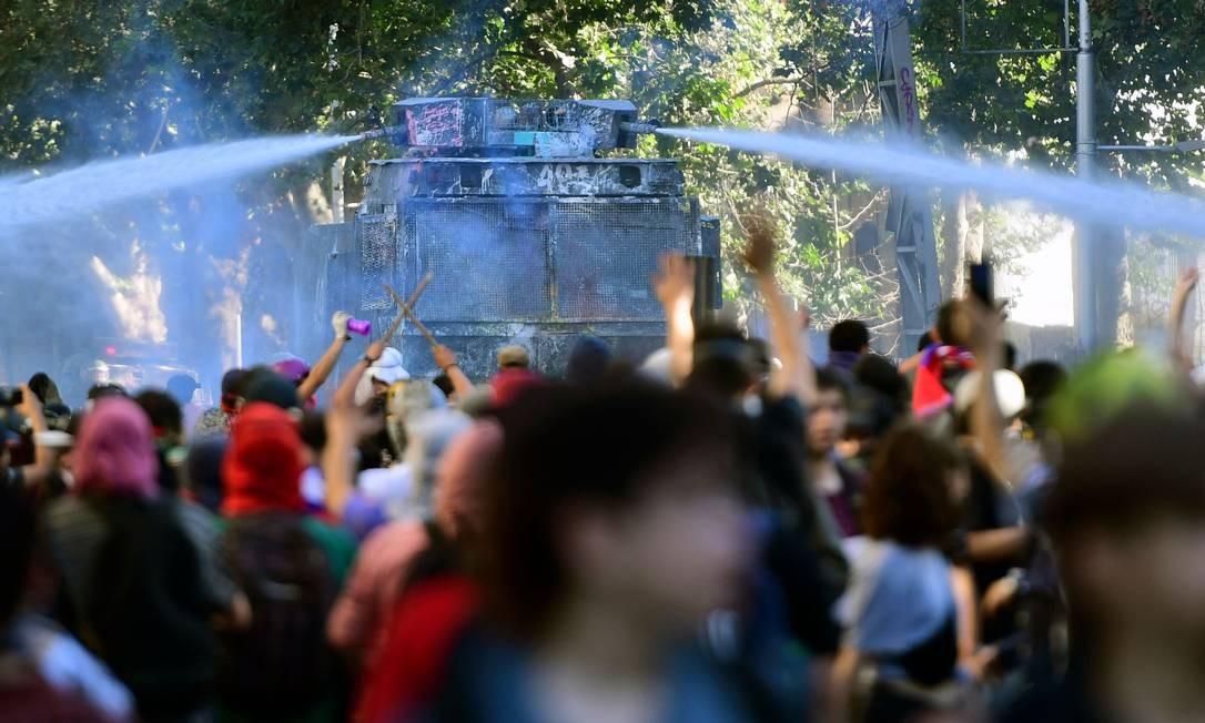 O batalhão de choque usou jatos d'água e gás lacrimogêneo para dispersar os manifestantes que se concentraram em vários pontos ao redor do centro comercial Foto: Martin Bernetti / AFP