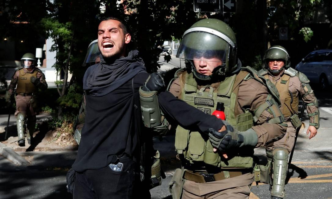 Membros das forças de segurança detêm um manifestante durante um protesto em Providencia, um bairro rico de Santiago Foto: Jorge Silva / Reuters