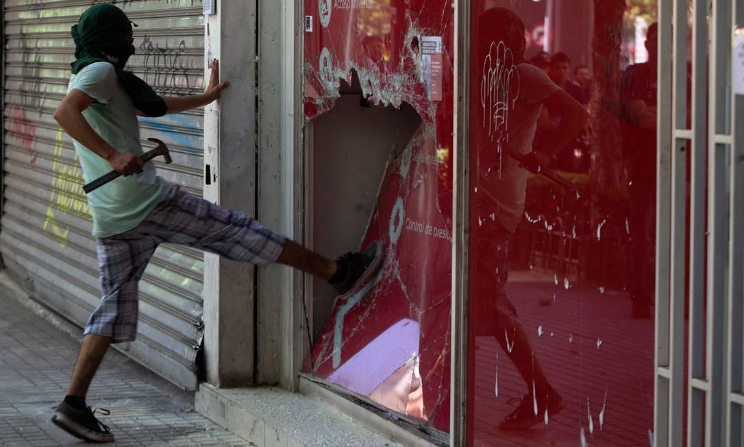 """Um manifestante quebra uma vitrine durante protesto em Santiago. Convocação por redes sociais tinha a seguinte mensagem: """"Chegou a hora de ir ao leste"""", área rica da capital, indicando que era hora de """"os empresários sentirem o descontentamento do povo"""" e a """"união das classes"""" Foto: Claudio Reyes / AFP"""