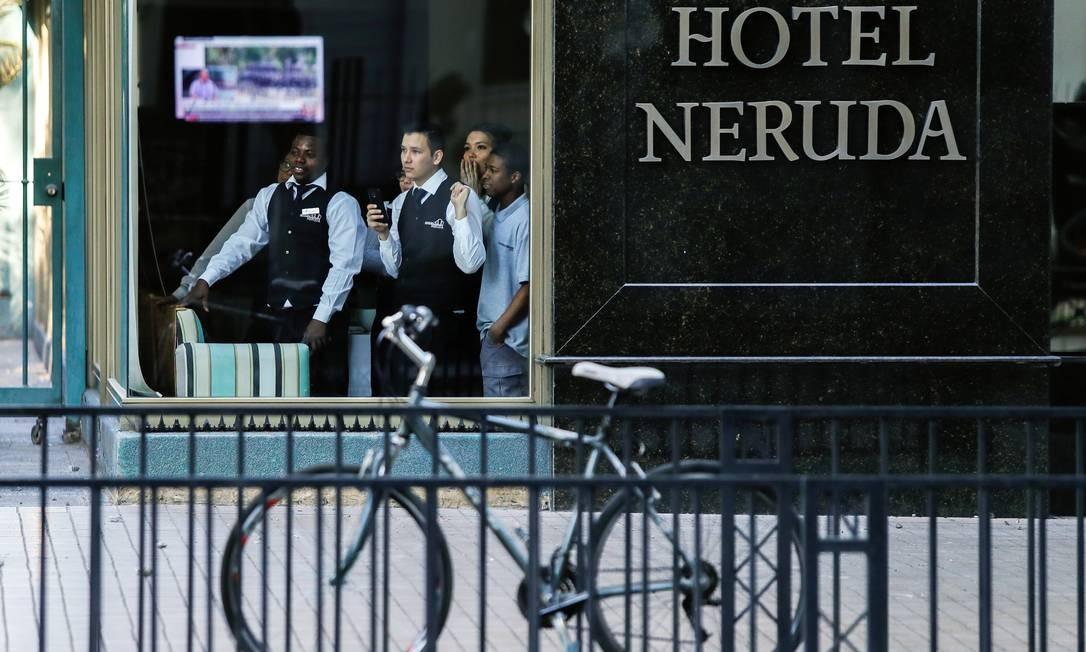 Funcionários de um hotel olham por trás de uma janela durante um protesto em Providencia, um bairro rico de Santiago. Após duas semanas e meia do início dos protestos, centenas de pessoas - a maioria jovens - chegaram ao centro comercial, o maior da América do Sul, para protestar por reformas sociais e contra o governo Foto: Jorge Silva / Reuters