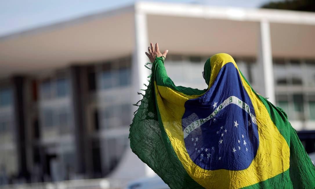 Manifestante contrário ao ex-presidente Lula protesta coberto por uma bandeira nacional em frente ao Supremo Tribunal Federal, em Brasília Foto: Ueslei Marcelino / Reuters
