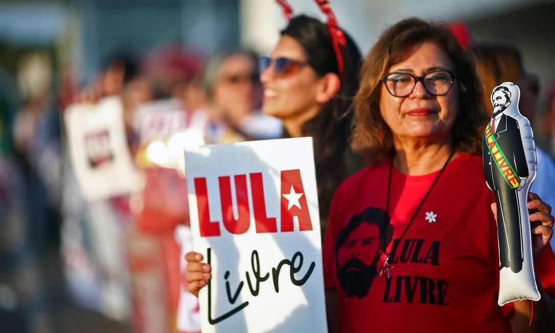 Apoiadores de Lula seguram faixas, cartazes e um boneco representando o ex-presidente, diante do STF, em Brasília, durante a votação decisiva sobre prisão em 2ª instância, em 7 de novembro Foto: Sergio Lima / AFP
