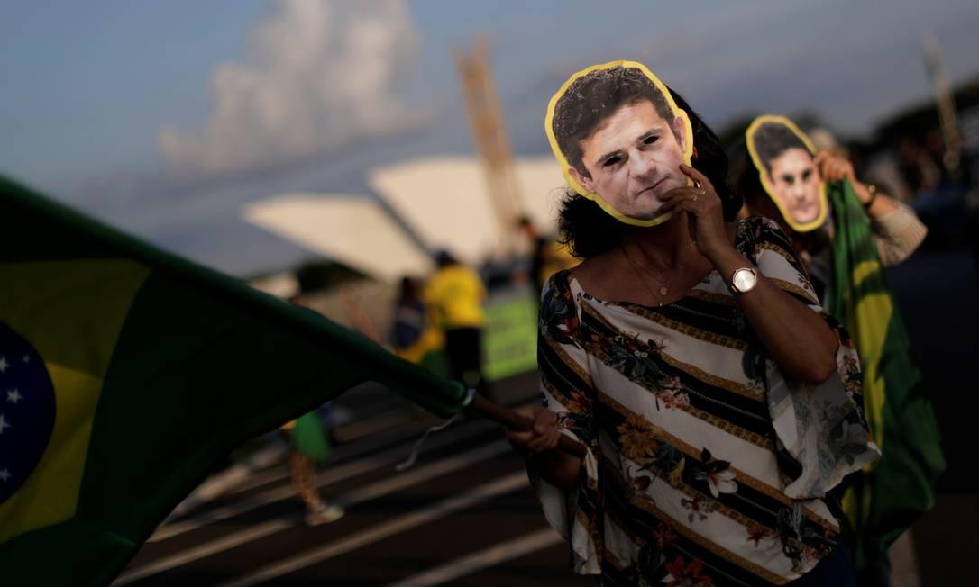 Com máscaras do ex-juiz e agora ministro da Justiça, Sergio Moro, manifestantes protestam contra a possível libertação do líder petista Foto: Ueslei Marcelino / Reuters