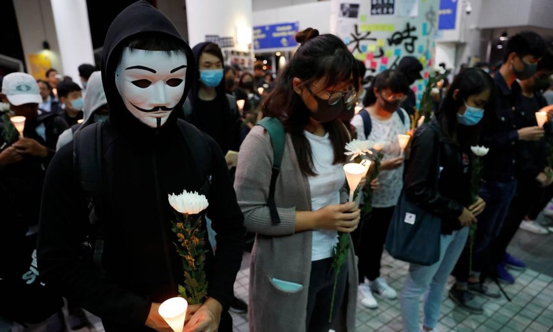 Manifestantes mascarados fazem vigília para o jovem Chow Tsz-lok Foto: TYRONE SIU / REUTERS