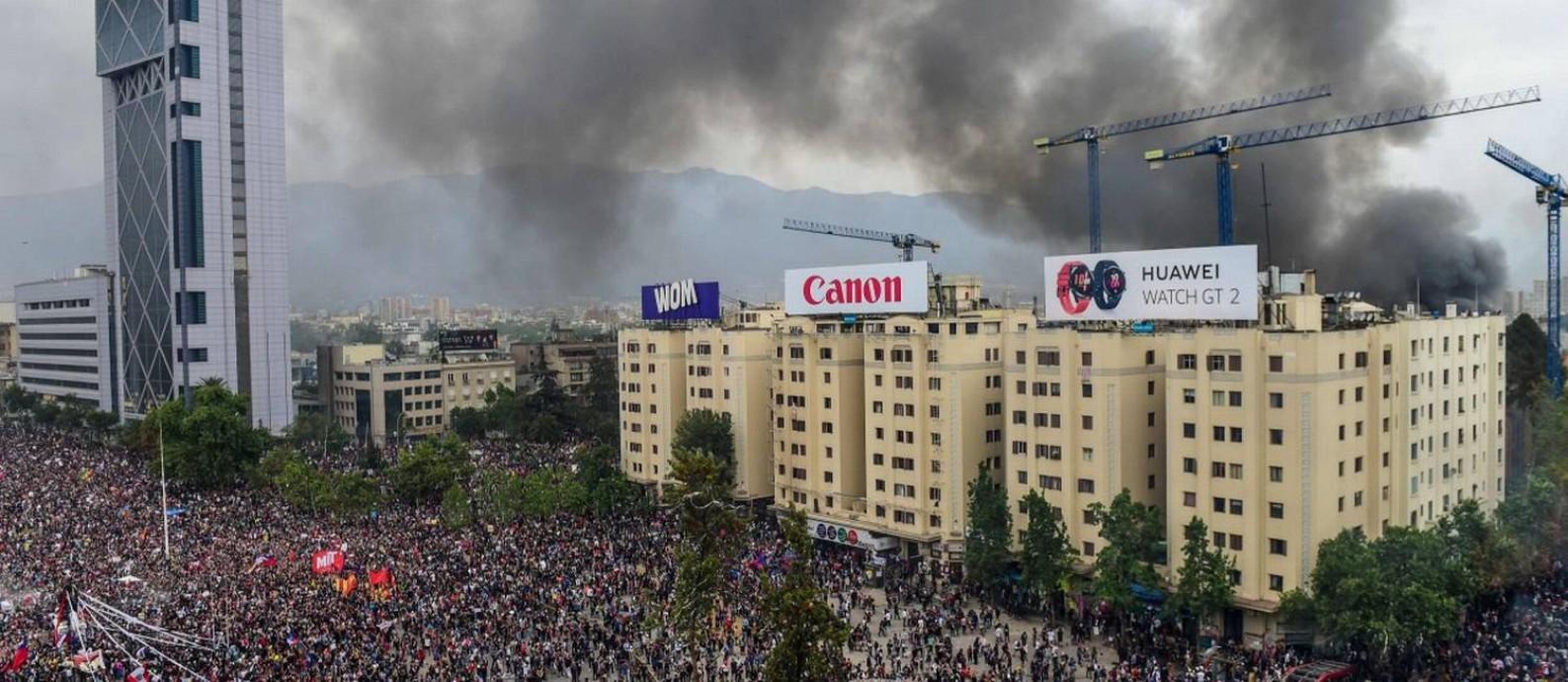 Fumaça da Universidade Pedro de Valdivia, incendiada por mascarados, é vista durante grande marcha na Praça Itália Foto: MARTIN BERNETTI / AFP