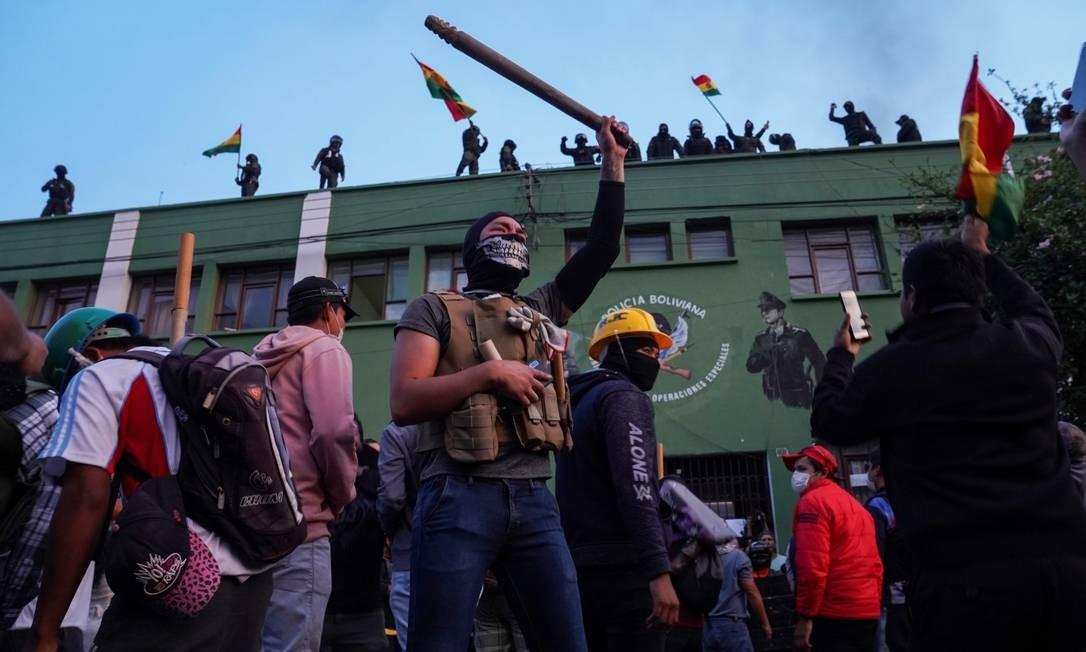 Policiais no telhado e manifestantes no chão protestam contra Morales em Cochabamba, Bolívia Foto: DANILO BALDERRAMA / REUTERS