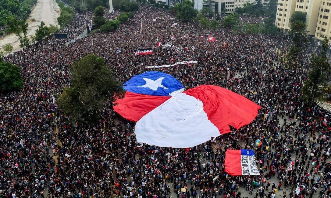 Manifestantes exibem uma bandeira gigante do Chile Foto: MARTIN BERNETTI / AFP