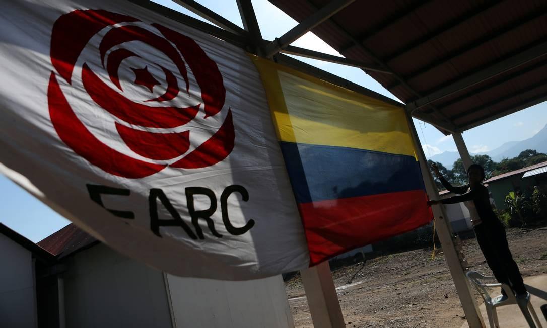 Mulher pendura uma bandeira colombiana ao lado da bandeira do partido político da Força Alternativa Revolucionária Comum (FARC) Foto: LUISA GONZALEZ / Reuters/02-09-2019