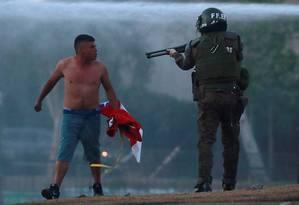 Policial aponta arma para manifestante em Santiago, Chile Foto: HENRY ROMERO / REUTERS/09-11-2019